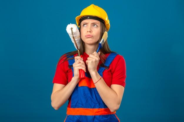 Jeune femme en uniforme de construction et casque de sécurité jaune pensant avec expression pensive visage sérieux tenant un rouleau à peinture et un pinceau debout sur fond bleu