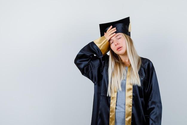Jeune femme en uniforme diplômé gardant la main sur la tête et ayant l'air en détresse
