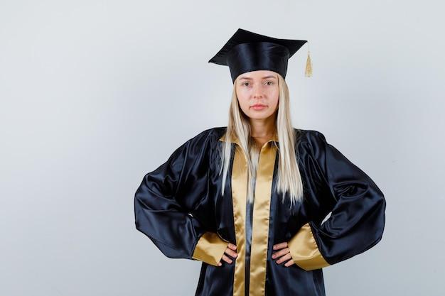 Jeune femme en uniforme diplômé gardant les mains sur la taille et ayant l'air confiant