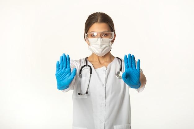 Jeune femme en uniforme médical sur fond blanc avec le geste de la main