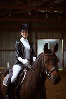 Jeune femme en uniforme spécial et casque à cheval sport équestre