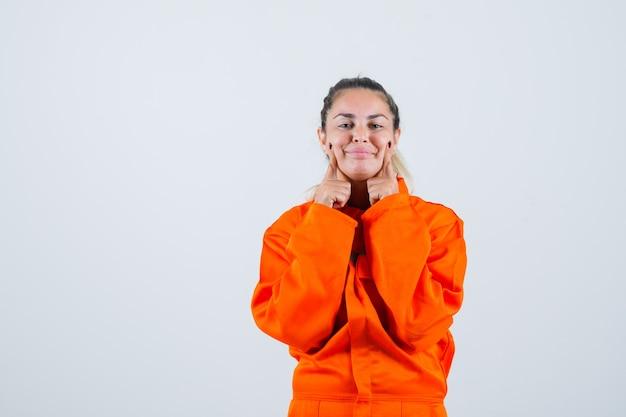 Jeune femme en uniforme de travailleur tenant les doigts sur ses joues et à la vue de face, adorable.