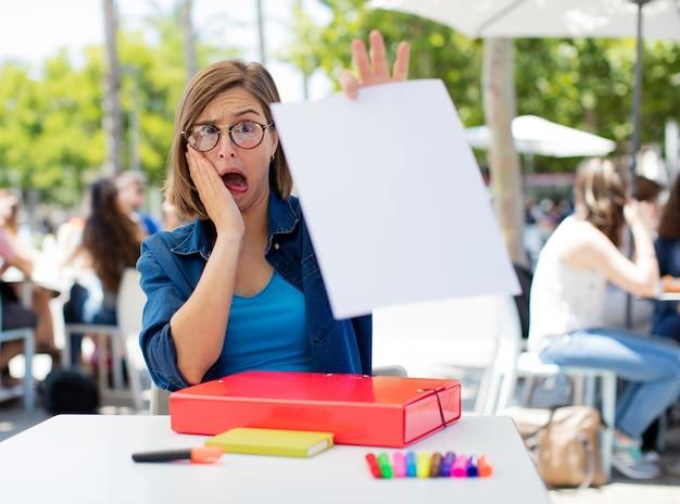 Jeune femme à l'université montrant une pancarte