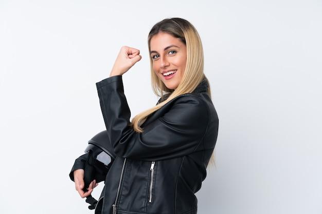 Jeune femme uruguayenne avec un casque de moto sur un mur blanc isolé faisant un geste fort