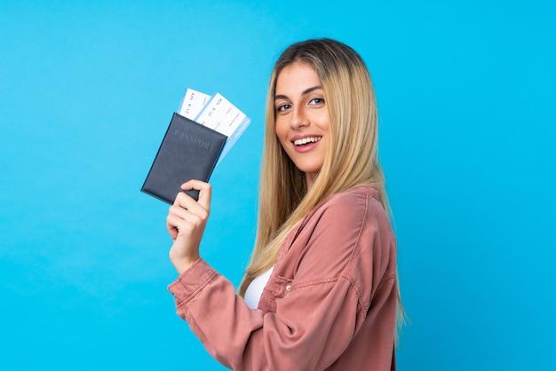 Jeune femme uruguayenne sur mur bleu isolé heureux en vacances avec passeport et billets d'avion