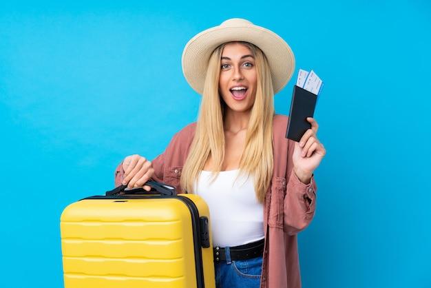 Jeune femme uruguayenne sur mur bleu isolé en vacances avec valise et passeport et surpris