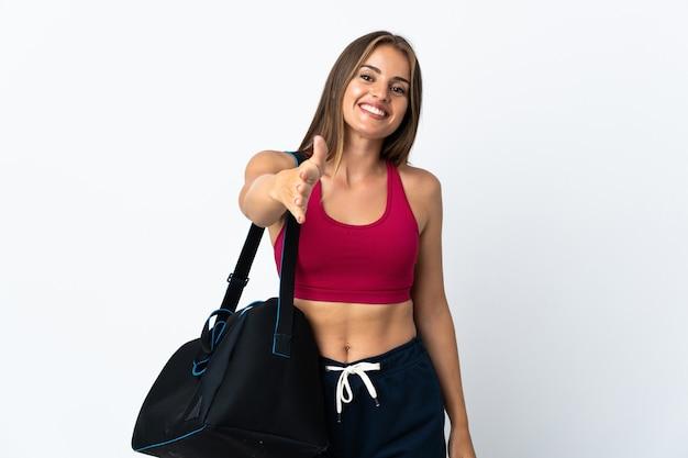 Jeune femme uruguayenne sport avec sac de sport isolé sur fond blanc se serrant la main pour conclure une bonne affaire