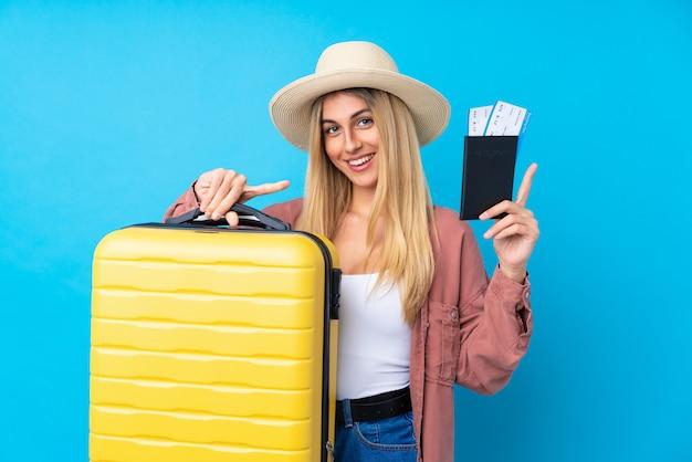 Jeune femme uruguayenne en vacances avec valise et passeport et surpris