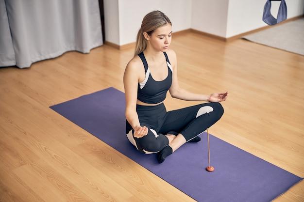 Jeune femme utilisant un bâton aromatique tout en faisant de l'exercice sur un tapis de sol dans une salle de cours de yoga lumineuse