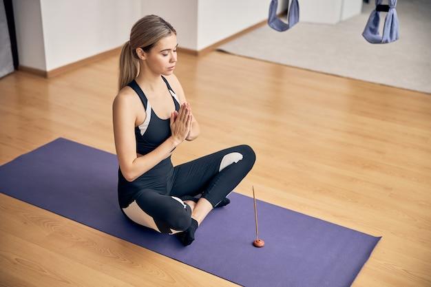 Jeune femme utilisant des bâtons aromatiques tout en faisant du yoga sur un tapis de sol dans une salle de cours de yoga
