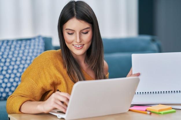 Jeune femme utilisant un ordinateur à la maison