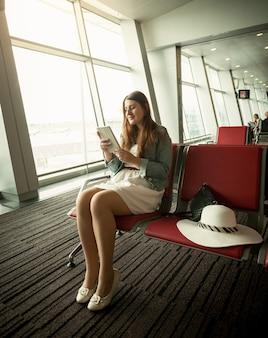 Jeune femme utilisant une tablette numérique en attendant le départ de l'avion