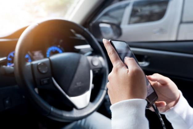 Jeune femme utilisant un téléphone intelligent pendant la conduite d'une voiture