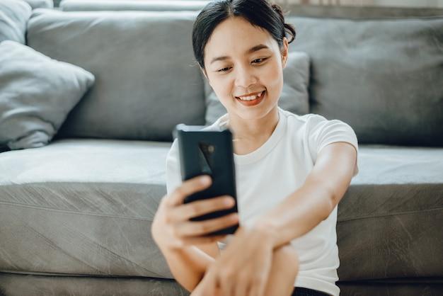 Jeune femme utilisant un téléphone portable pour se connecter à la communication dans le cyberespace, tenant un smartphone et un message texte, des femmes satisfaites de la technologie intelligente, un mode de vie féminin pour les affaires en ligne