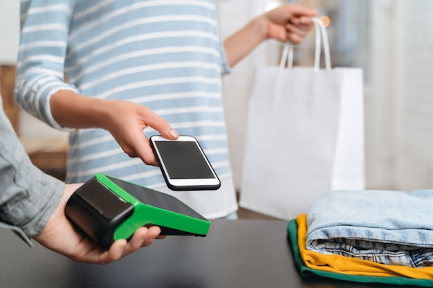 Jeune femme utilisant un terminal de paiement et un téléphone portable avec technologie nfc pour payer sans numéraire