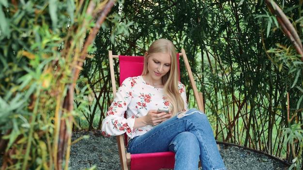 Jeune femme, utilisation, smartphone, dans, plante, gazebo.