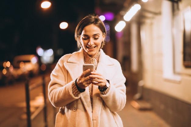 Jeune femme, utilisation, téléphone, dehors, rue nuit