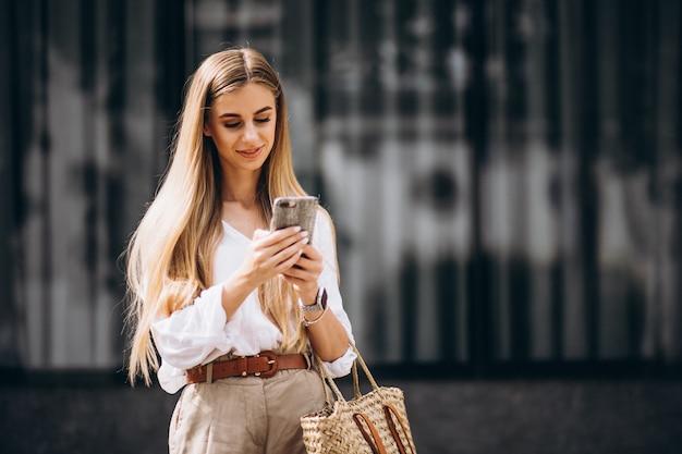 Jeune femme, utilisation, téléphone, dehors, ville