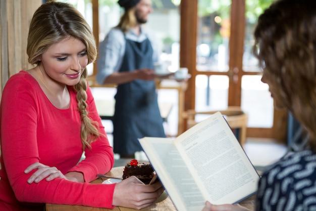 Jeune femme, utilisation, téléphone, quoique, ami, lecture livre, dans, café-restaurant