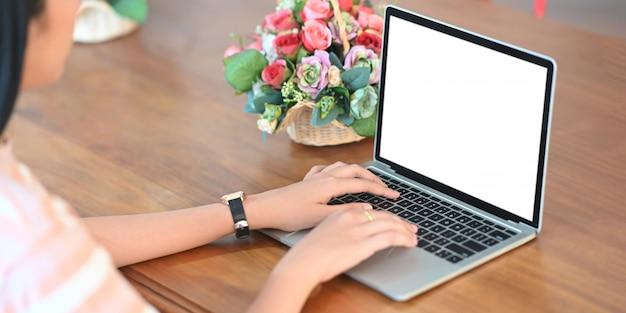 Une jeune femme utilise un ordinateur portable à écran blanc blanc à la table de travail en bois