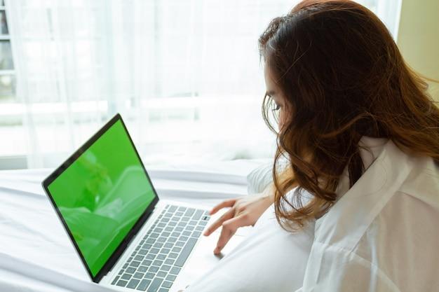 Jeune femme utilise un ordinateur portable sur le lit