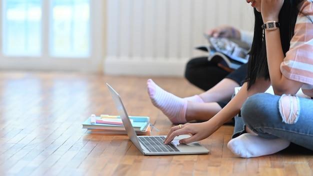 Une jeune femme utilise un ordinateur portable qui met sur le sol du salon