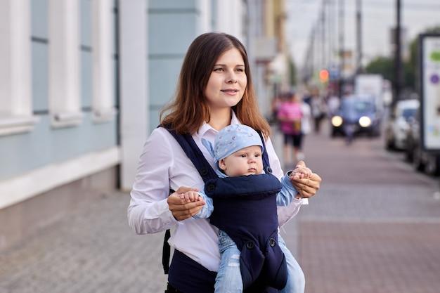 Une jeune femme utilise un porte-bébé ou une écharpe en marchant dehors avec son fils de quatre mois