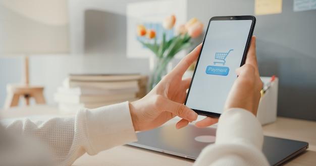 Une jeune femme utilise un produit d'achat en ligne pour commander un téléphone portable et paie des factures avec une application bancaire avec une transaction réussie. restez à la maison, activité de quarantaine, activité amusante pour la prévention des coronavirus.