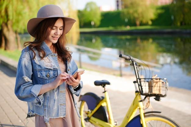 Jeune femme utilise un smartphone pour louer un vélo dans la ville en été