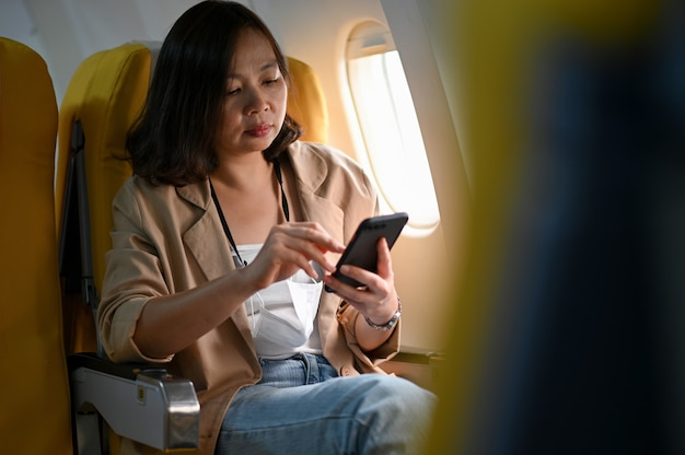 Jeune femme utilise des smartphones lors de voyages en avion.