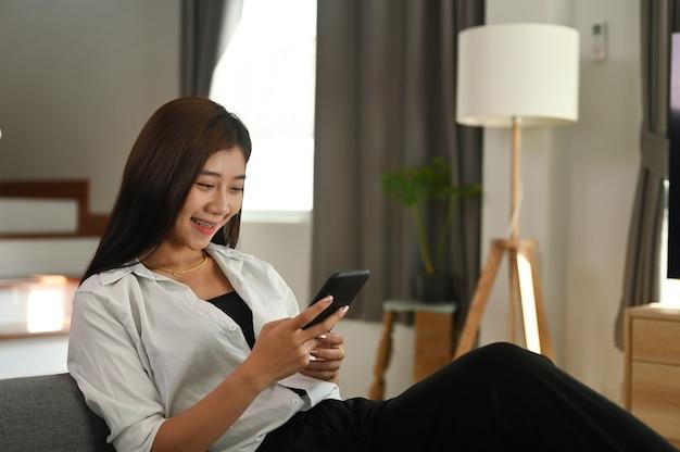 Une jeune femme utilise un téléphone intelligent tout en se reposant sur un canapé dans le salon