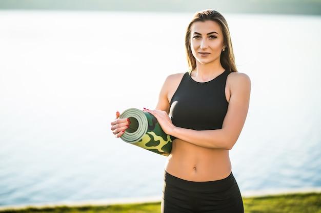 Une jeune femme va s'entraîner sur la plage avec un tapis de yoga. extérieur.