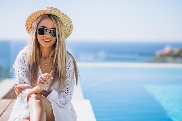 Jeune femme en vacances au bord de la piscine
