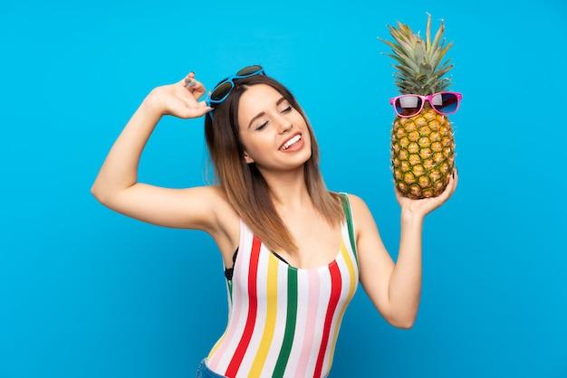 Jeune femme en vacances d'été sur fond bleu, tenant un ananas avec des lunettes de soleil