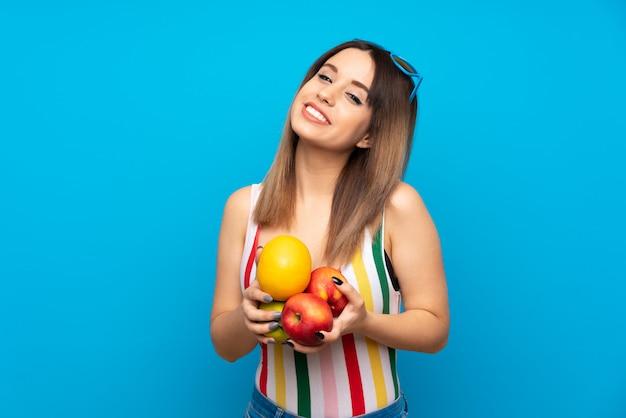 Jeune femme en vacances d'été sur fond bleu, tenant des fruits