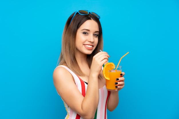 Jeune femme en vacances d'été sur mur bleu avec cocktail