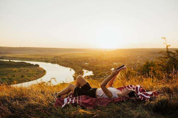 Jeune femme en vacances lit un livre sur une colline au coucher du soleil.