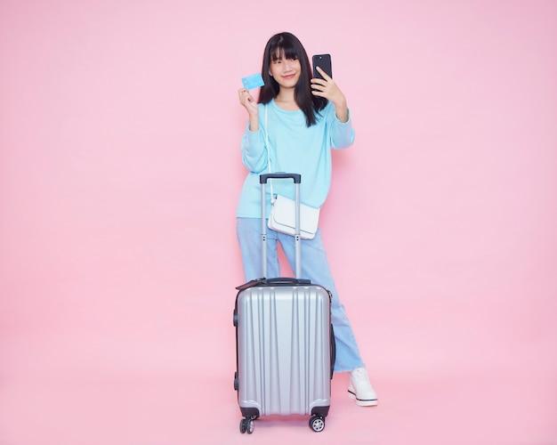 Jeune femme avec valise et à l'aide de téléphone portable avec carte de crédit pour payer.