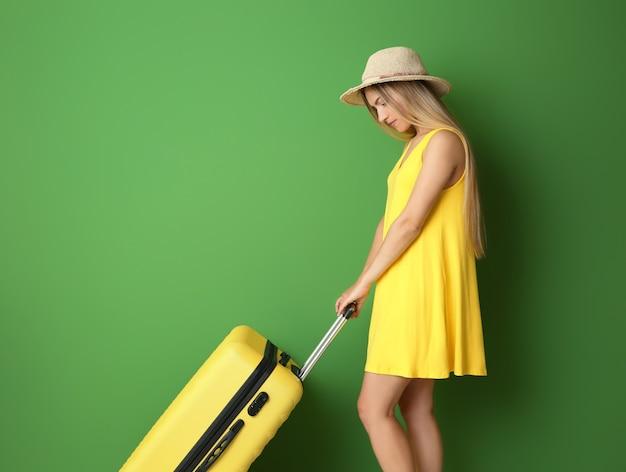 Jeune femme avec valise sur fond de couleur. concept de surpoids de bagages