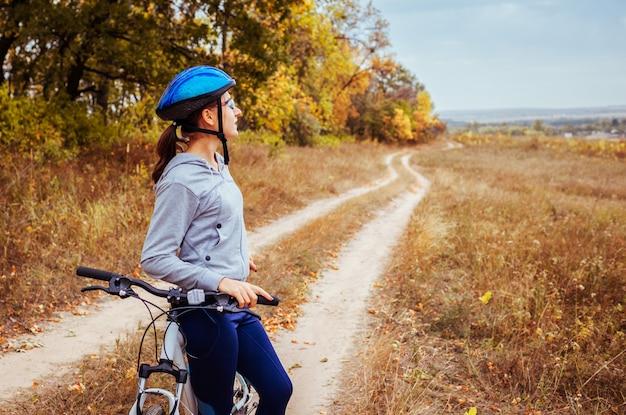 Jeune femme à vélo dans le champ d'automne