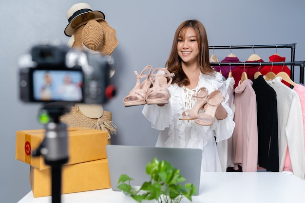 Jeune femme vendant des chaussures et des vêtements en ligne par caméra en direct streaming, commerce électronique en ligne à la maison