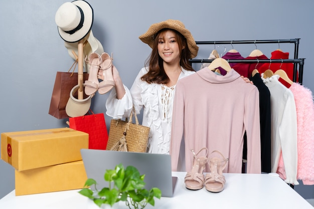 Jeune femme vendant des vêtements et accessoires en direct streaming en ligne, commerce électronique en ligne à la maison