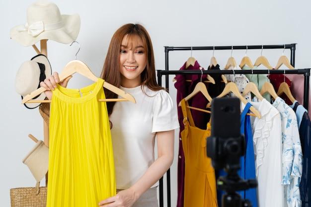 Jeune femme vendant des vêtements et accessoires en ligne par smartphone streaming en direct, commerce électronique en ligne à la maison