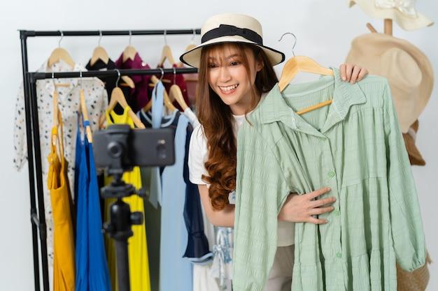 Jeune femme vendant des vêtements et un chapeau en ligne par smartphone en direct streaming, commerce électronique en ligne à la maison