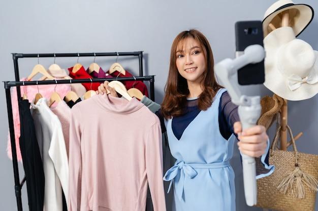 Jeune femme vendant des vêtements en ligne par smartphone en direct, commerce électronique en ligne à la maison