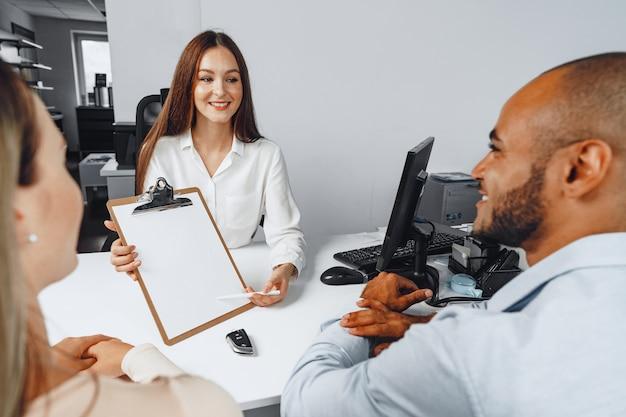 Jeune femme vendeur de voitures montrant un contrat à quelques acheteurs de voitures dans son bureau