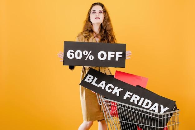 Jeune femme a vendredi noir 60% de réduction signe avec chariot plein de sacs à provisions et ruban de signalisation isolé sur jaune