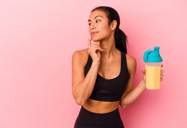 Jeune femme vénézuélienne buvant un shake protéiné isolé sur fond rose détendu