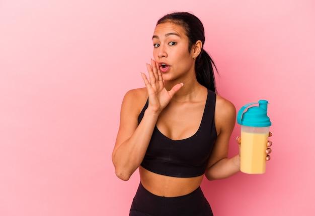 Jeune femme vénézuélienne buvant un shake protéiné isolé sur fond rose dit un secret