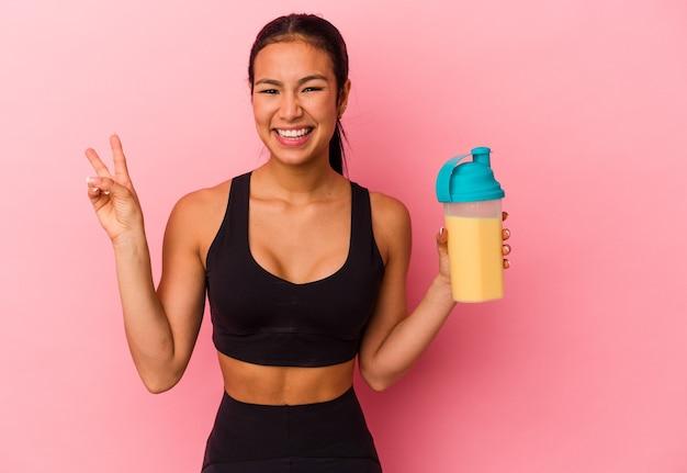 Jeune femme vénézuélienne buvant un shake protéiné isolé sur fond rose joyeux